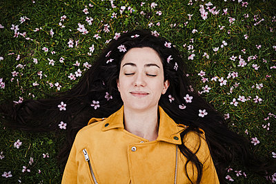 Relaxed woman with flowers in hair lying on grass - p300m2274701 by Eva Blanco