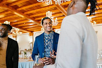 Cheerful male friends talking and celebrating at banquet - p300m2275020 by Ezequiel Giménez