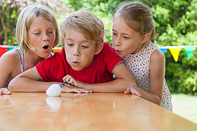 Children blowing cotton ball on garden table - p300m838593f by Nico Hermann