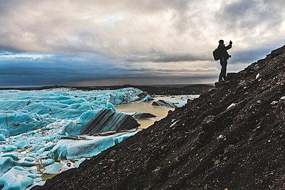 Man on hillside, photographing view, Svinafellsjokull glacier, Svinafellsjokull. Iceland - p429m1418142 by William Perugini