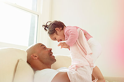 Mid adult man on sofa holding up baby daughter - p429m1418465 by Emma Kim