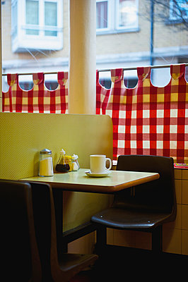 A restaurant with red and white checkered curtains on the window and a yellow wall; London, England - p442m936504 by Ingrid Rasmussen