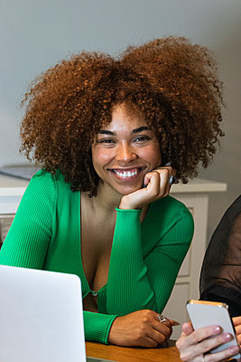 Barcelona, Spain. Two young women having fun at home. Women, diversity, working, laptop, afro hair, blonde, bed, coworking, businesswoman, eating, fruit, living room, smartphone, professional, two, together, friendship, friends, technology - p300m2294135 von NOVELLIMAGE
