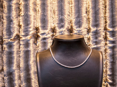 Close-up of necklace displayed on mannequin against velvet in store - p301m1148209 by Etienne Girardet