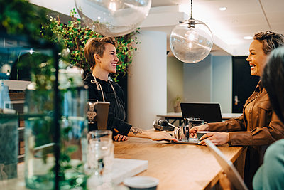 Smiling female customer talking with businesswoman in coffee shop - p426m2259371 by Maskot