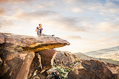 Caucasian woman stretching on rock formation - p555m1311600 by Mike Kemp