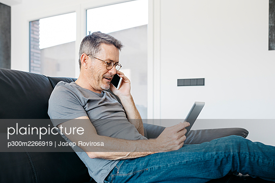 Mature man talking on smart phone while using digital tablet on sofa at living room - p300m2266919 by Josep Rovirosa