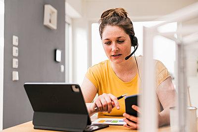 Female entrepreneur video conferencing through digital tablet while sitting at desk - p300m2267561 by Uwe Umstätter