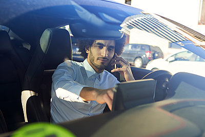Businessman using GPS while talking on smart phone in car seen through windshield - p300m2267605 by Veam