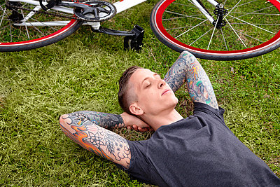 Young tattooed man lying on grass - p429m802534 by Cultura