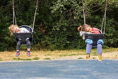 Girls sitting in still swings - p555m1303596 by Adam Hester