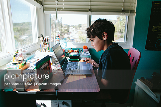 Ten year old boy takes a zoom call on his laptop for homeschool - p1166m2201541 by Cavan Images