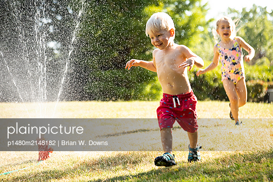 Portrait of a young girl and boy playing in a backyard sprinkler - p1480m2148182 by Brian W. Downs
