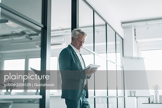 Businessman using digital tablet while standing by glass wall at office - p300m2226129 by Gustafsson