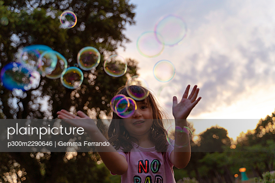 Girl playing with soap bubbles during sunset - p300m2290646 by Gemma Ferrando