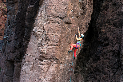 Full length of female hiker climbing on mountain - p1166m1568941 by Cavan Images