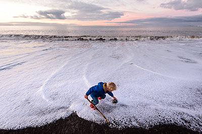 Little boy picking up rock at beach in New Zealand - p1166m2137166 by Cavan Images