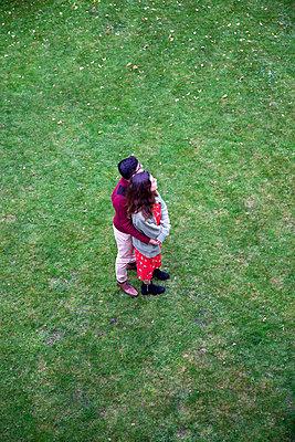 Junges Paar umarmt sich auf einer Rasenfläche - p1248m2141932 von miguel sobreira