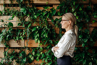 Businesswoman at wall with climbing plants - p300m2023759 by Joseffson