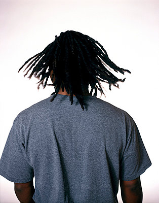 Back of African American male's head with dreadlocks swinging - p3720325 by James Godman