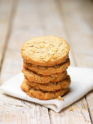 Stack of apple crumble cookies on tea towel - p429m1095486f by Diana Miller