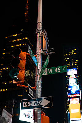 View of street signs on traffic light pole - p623m2186243 by Pablo Camacho