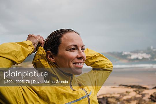Smiling woman wearing raincoat at beach during rainy season - p300m2225176 by David Molina Grande