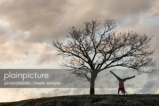 Silhouette of woman doing handstand - p312m2092055 by Fredrik Schlyter