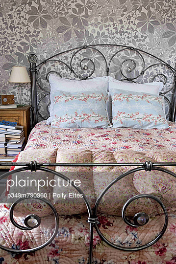 Vintage metal bed with quilts and metallic floral wallpaper in bedroom of London home - p349m790960 by Polly Eltes