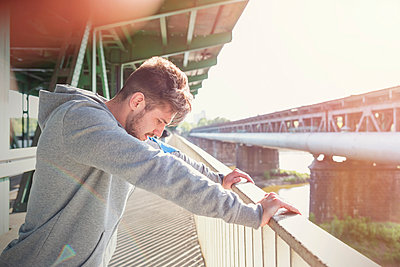 Male runner stretching, leaning against sunny urban railing - p1023m2161281 by Rafal Rodzoch