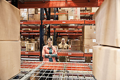 A Caucasian male and female warehouse workers surrounded by boxed products on racks in a distribution warehouse. - p1100m2002280 by Mint Images