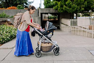 Mother fixing blanket of baby in stroller - p1166m2078491 by Cavan Images