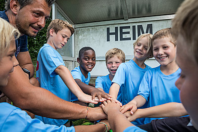 Coach and young football players huddling - p300m1580932 by Fotoagentur WESTEND61