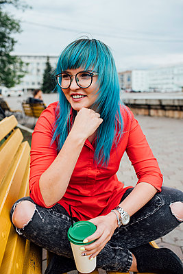 Portrait of smiling young woman with dyed blue hair sitting on a bench with beverage - p300m2062957 by Vasily Pindyurin