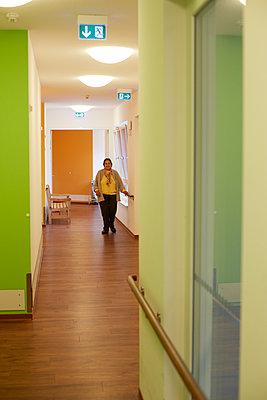 Age demented senior woman on corridor in a nursing home - p300m2219209 by Heinz Linke