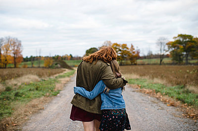 Mother and daughter hugging on dirt road, Lakefield, Ontario, Canada - p429m1407785 by Erin Lester