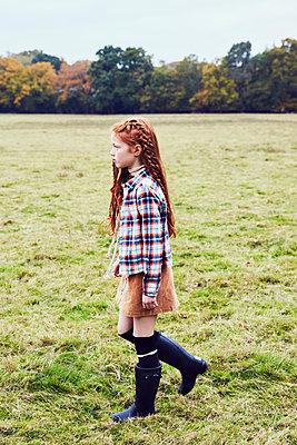 Young girl, walking through field - p429m1407789 by Emma Kim