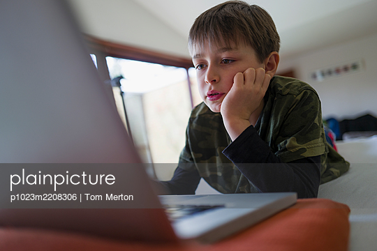 Focused boy e-learning at laptop - p1023m2208306 by Tom Merton