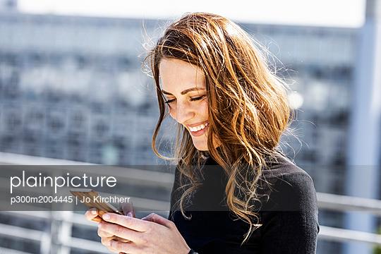 Portrait of smiling woman using  smartphone - p300m2004445 von Jo Kirchherr