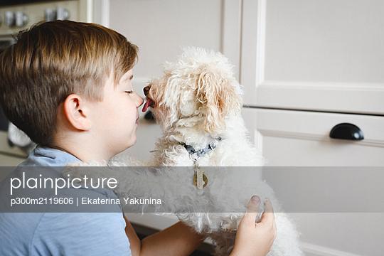 Boy playing with his dog at home - p300m2119606 by Ekaterina Yakunina