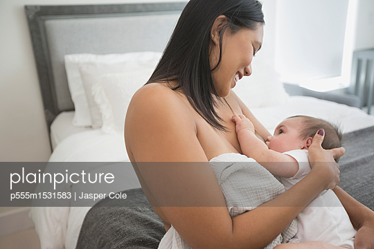 Woman sitting on bed breast-feeding baby son - p555m1531583 by Jasper Cole