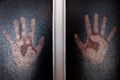 Hands against a translucent glass door or window - p1423m2089392 von JUAN MOYANO