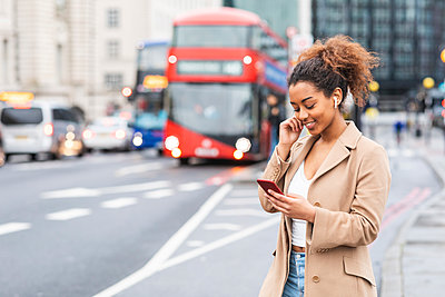 Smiling young woman with cell phone and earbuds in the city, London, UK - p300m2166974 by William Perugini