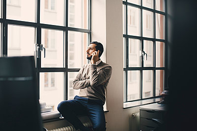 Male entrepreneur talking on smart phone by window in creative office - p426m2270524 by Maskot