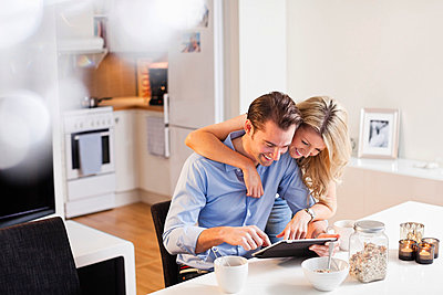 Happy couple using digital tablet at breakfast table - p426m803239f by Maskot
