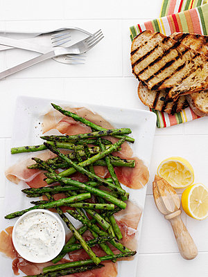 Plates of ham, asparagus, and bread - p42919220 by Brett Stevens