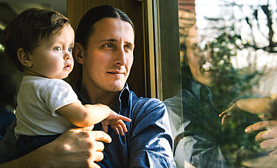 Mature man and baby son looking through window - p429m1227232 by Bonfanti Diego