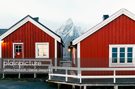 Red huts and snowcapped mountain at the coast, Hamnoy, Lofoten, Norway - p300m2166328 by Daniel González