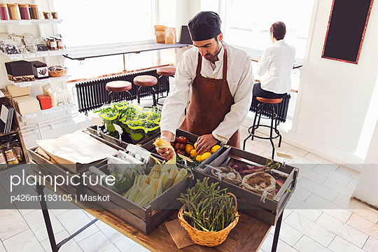 High angle view of male owner arranging vegetables at grocery store - p426m1193105 by Maskot