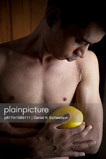 Inder mit nacktem Oberkörper hält eine Mango - p817m1589111 von Daniel K Schweitzer